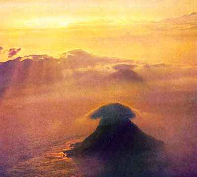 A golden sunset over a cloudy sea; steep conical islands, each with a dark lenticular cloud for a cap.