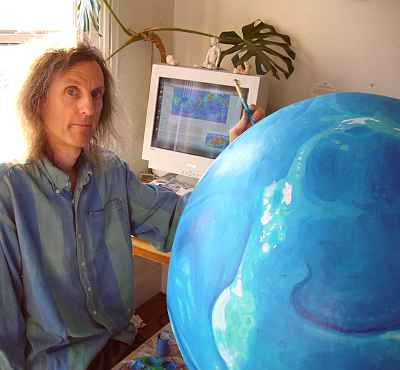 Chris Wayan sitting by Lyr, a big papier-mache planet in blue and white (the land's still unpainted).